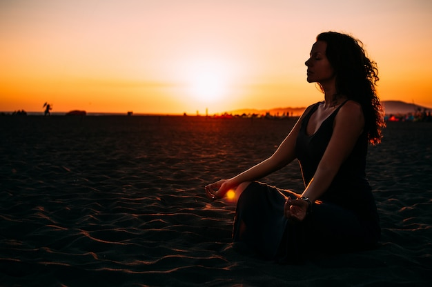 ビーチでのヨガ。蓮の瞑想の女性が日没でポーズします。