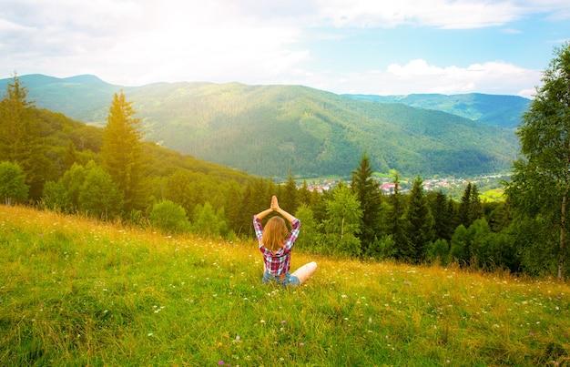 Йога в горах. красивая девушка медитирует в асане. удивительная летняя природа вокруг. концепция гармонии и страсти к путешествиям. хипстерское путешествие. стильная женщина наслаждается жизнью.