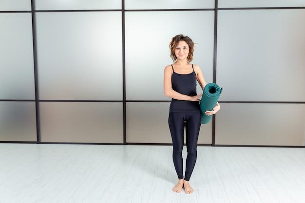 Йога в помещении. молодая женщина в спортивной одежде, готовой к тренажерному залу и йоге, держа зеленый коврик.