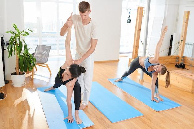 Инструктор по йоге корректирует позу женщины в классе