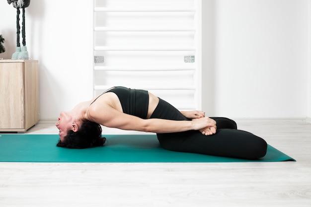 Инструктор по йоге занимается йогой у себя дома