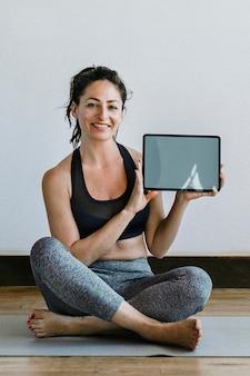 Инструктор по йоге показывает обои для мобильного телефона на цифровом планшете