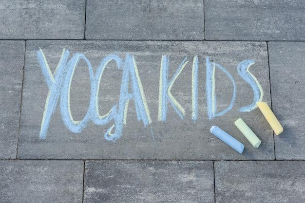 色付きのクレヨンで舗装スラブに子供たちによって書かれたヨガの子供たちのテキスト