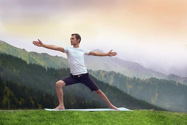 Yoga man fitnes in mountain.