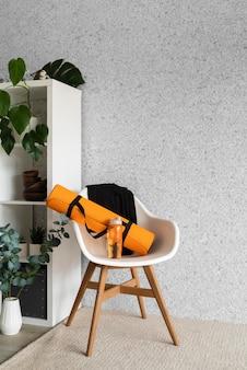 Коврик для йоги и бутылка с водой на стуле