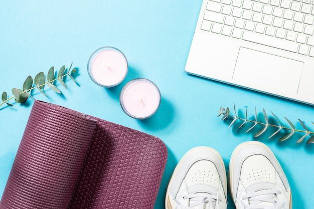 Коврик для йоги, ароматические свечи, веточки эвкалипта и ноутбук на синем пастельном столе.