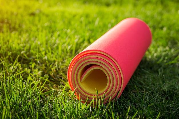 夏の公園の芝生の上のヨガマット。スポーツ用品