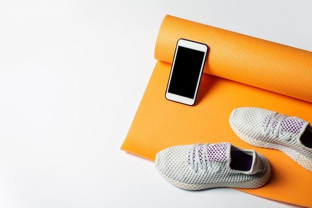 Йога коврик, подметать и телефон на белом фоне. спорт, йога и тренировки. вид сверху