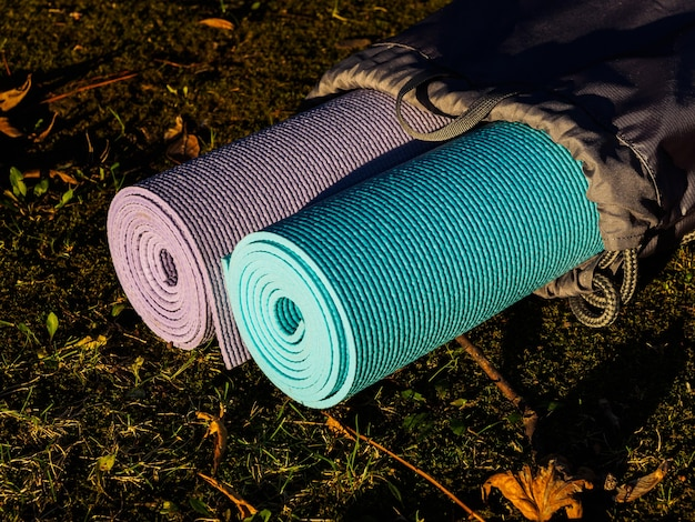 Коврики для йоги в сером покрытии на траве.