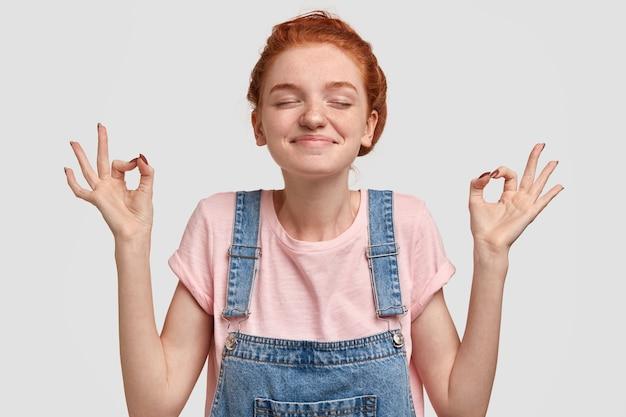 Concetto di yoga e meditazione. calma e contenta donna lentigginosa con pelle morbida, sta con gli occhi chiusi allarga le mani nel gesto zen, indossa una maglietta casual e una tuta di jeans, isolata sopra il muro bianco