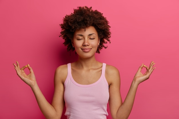 Yoga and meditation concept. relaxed satisfied dark skinned woman holds hands in mudra gesture, feels peaceful after hard day, keeps eyes closed, controls her feelings, stands in lotus pose.
