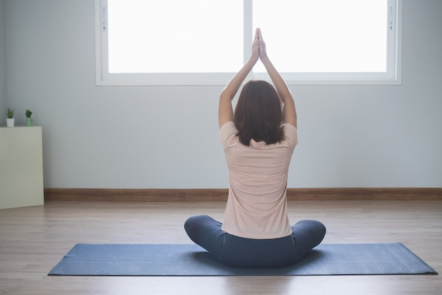 Yoga and meditation lifestyles. back view of young beautiful woman practicing yoga in the living room at home.