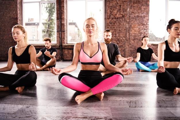 フィットネスセンターで蓮華座の若いリラックスした人々のヨガ瞑想