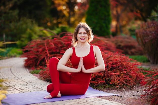 Поза медитации йоги, сосредоточенная красивая женщина в красной ткани