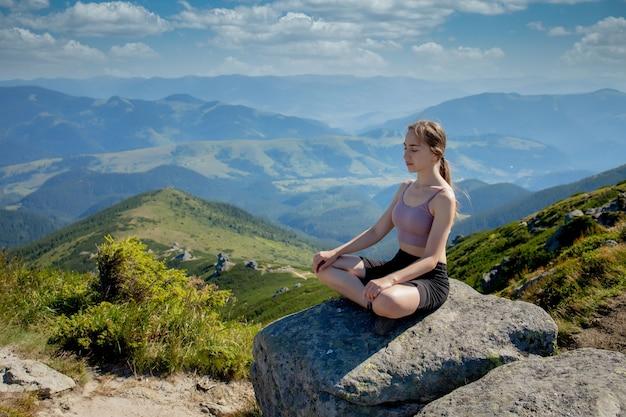 ヨガ、瞑想。山でバランスの取れた、瞑想と禅エネルギーヨガを実践している女性。