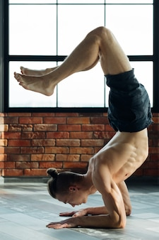 Yoga for men. sport fitness and athletic lifestyle. strong body and toned muscles. man exercising asana in gym.