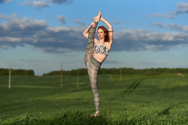 Yoga in the natural. red-haired woman practices yoga outdoors.  spiritual and emotional concept.