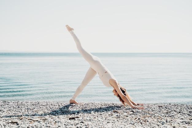 해변에서 요가 바다의 해안선에서 요가를 연습하는 여자 바다에서 휴식을 취하는 아름다운 소녀