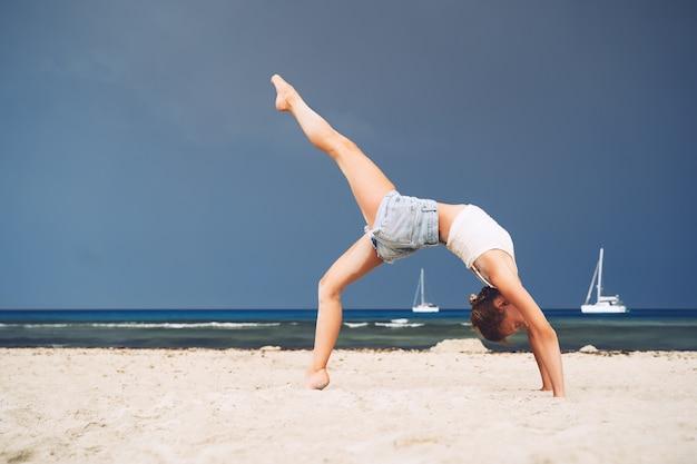 해변에서 요가 바다의 해안선에서 요가를 연습하는 여자