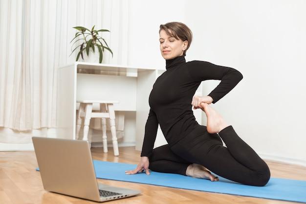 ノートパソコンでヨガをオンラインで。女性が自宅で瞑想しています。