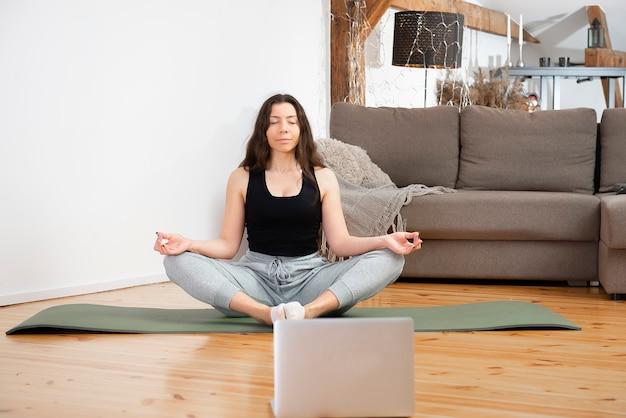 Йога онлайн. расслабленная молодая женщина медитирует перед ноутбуком дома, сидя в позе лотоса