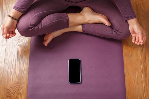 自宅のジムでフィットネスアプリを使用して、スマートフォンでヨガのオンライントレーニングトレーニングを行います。オンラインヨガと瞑想の練習。スマートフォンの画面に配置