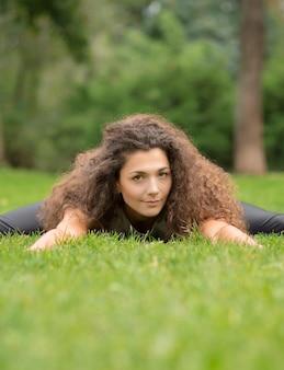 サマーパークでのヨガやフィットネス。緑の草の上に横たわっている長い巻き毛を持つ若い女性の正面図