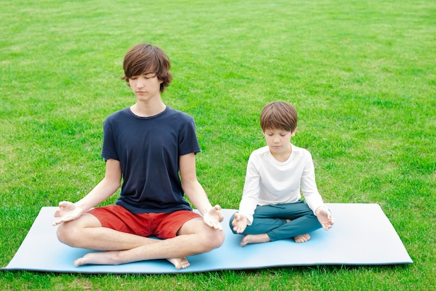 Yoga outdoor. children sit in a lotus position on the green grass. copy space.