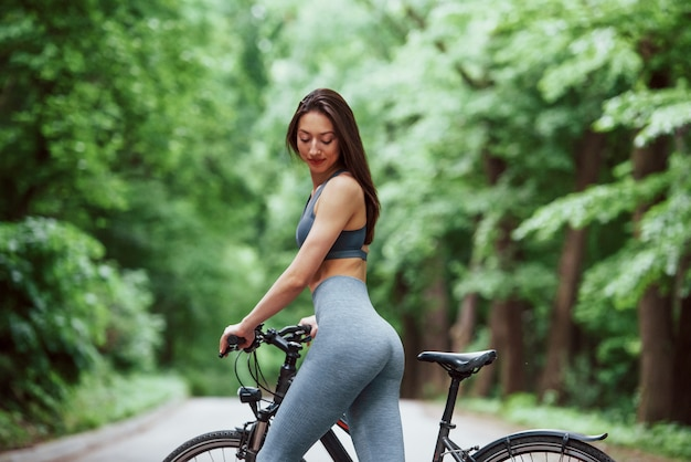 In yoga pants. female cyclist standing with bike on asphalt road in the forest at daytime