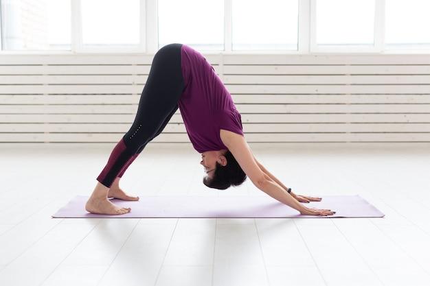 Йога, концепция людей - женщина средних лет занимается йогой и пытается выполнить асану.