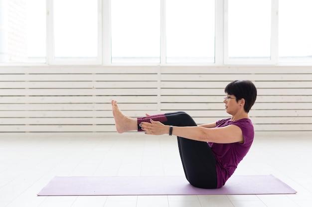Йога, люди концепции. женщина средних лет занимается йогой в тренажерном зале.