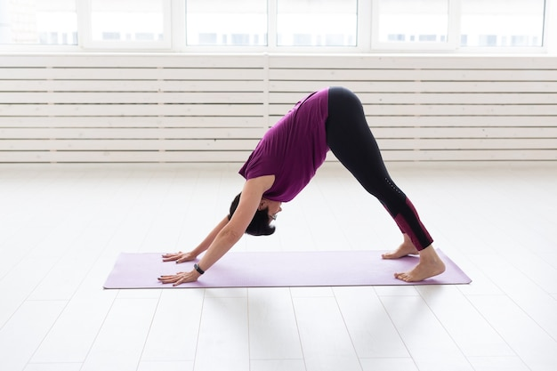 Yoga, people concept. a middle-aged woman doing a yoga in the gym