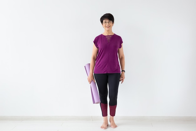 Yoga, people concept - portrait of a middle age woman after yoga with her mat on white background