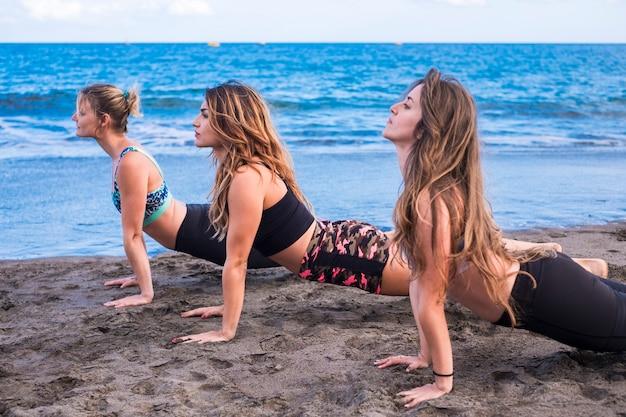 요가 필라테스 여성 활동 여가 활동 야외 파도 근처 해변에서. 하늘과 바다, 세 명의 아름다운 소녀가 함께 스포츠 스트레칭을하고 있습니다. 건강한 신체와 라이프 스타일 컨셉