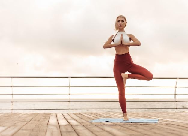 Практика йоги на рассвете молодая женщина-йогин стоит в позе с намастэ