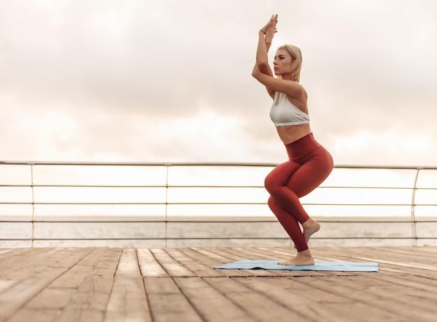 Практика йоги на рассвете молодая женщина-йог стоит в позе дерева