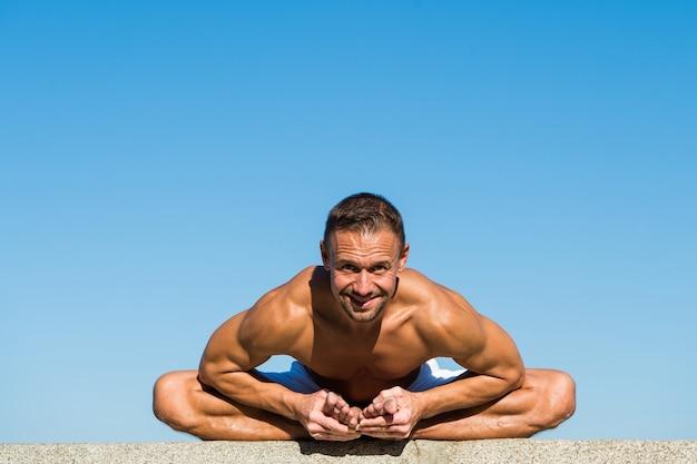 ヨガの練習は、調和とバランスを見つけるのに役立ちますヨガの青空の背景を練習している男性に到達しました