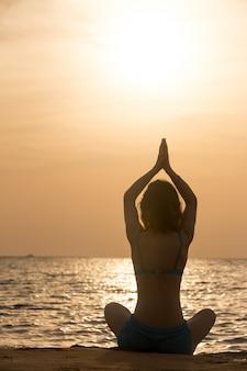 La pratica dello yoga in riva del mare