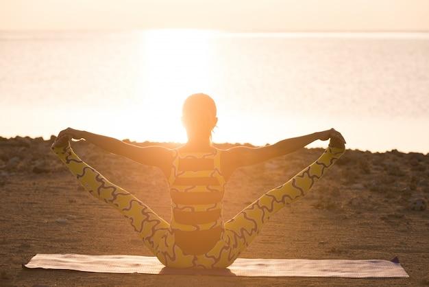 Pratica yoga. donna che fa asana all'alba