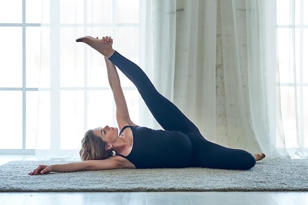 ヨガ。自宅でヨガ瞑想を実践している妊婦。健康ライフスタイルのコンセプトとベビーケア。
