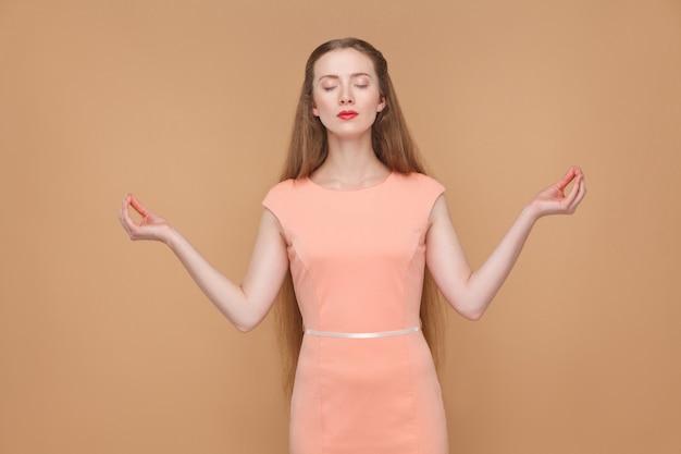 요가, 휴식 및 명상. 핑크 드레스에 화장과 긴 머리를 가진 감정적 인 귀엽고 아름다운 여성의 초상화. 실내, 스튜디오 촬영, 밝은 갈색 또는 베이지색 배경에 격리되어 있습니다.