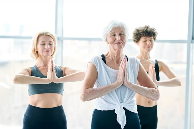 Yoga relaxing. women group meditating next to a large window