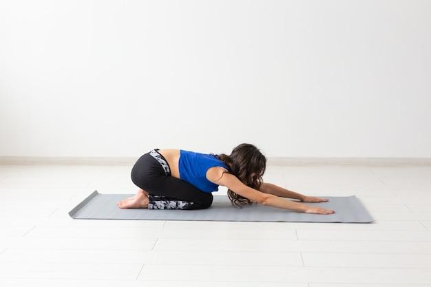 Концепция йоги, спорта, отдыха и людей - молодая женщина, практикующая йогу в помещении