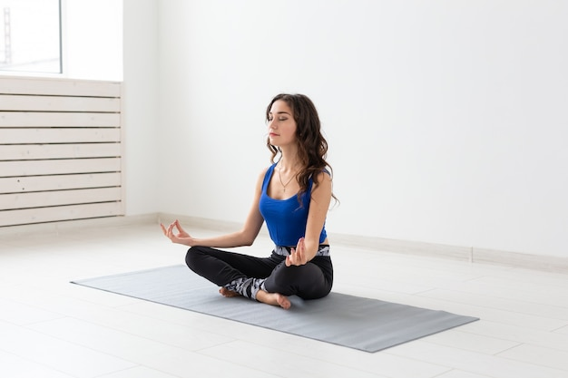 Йога, спорт, отдых и люди концепции. молодая женщина занимается йогой в помещении.