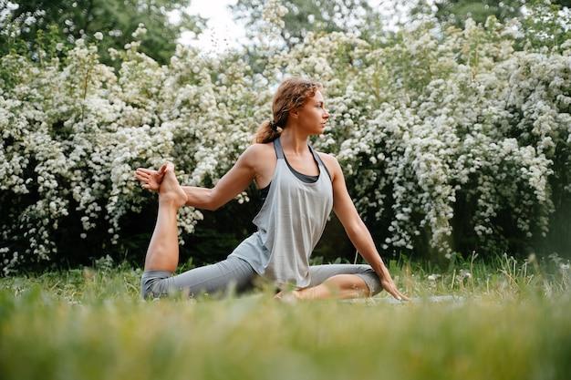 요가 스트레칭 운동은 공원에서 야외 척추 건강을 위해 허리를 스트레칭하는 젊은 여성에 의해 수행됩니다.