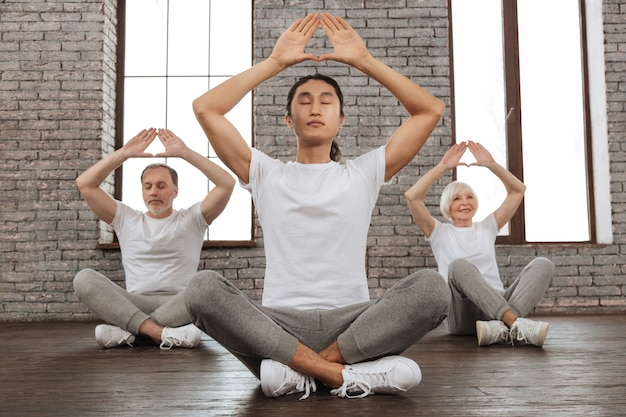 Yoga style. young asian instructor holding his back straight crossing both legs while keeping arms above head