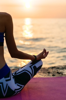 Yoga at sunrise. back view of a half body of sportive woman, sitting in lotus pose