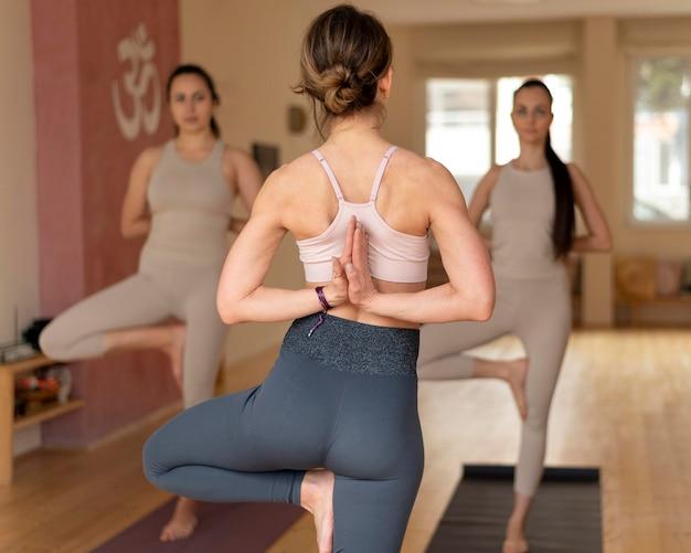 Insegnante di yoga in classe che insegna agli assistenti