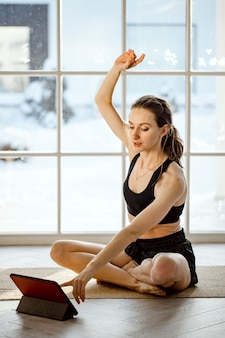 Учитель йоги проводит виртуальный урок йоги дома на видеоконференции.