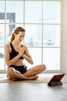 Учитель йоги проводит виртуальный урок йоги дома на видеоконференции